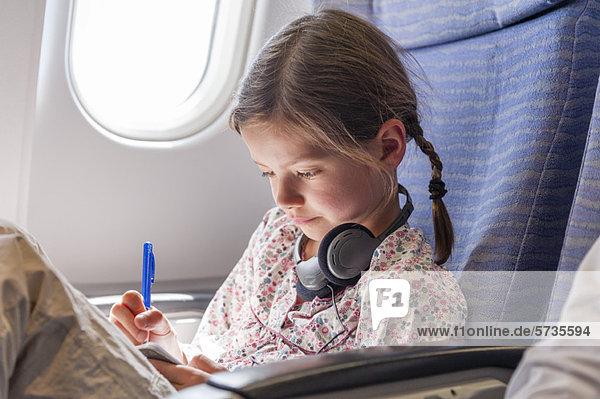 Mädchen schreiben im Notizbuch im Flugzeug Mädchen schreiben im Notizbuch im Flugzeug