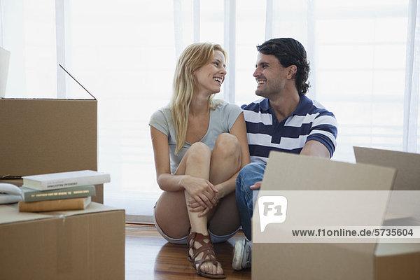 Paar auf dem Boden sitzend in neuem Haus mit Pappkartons