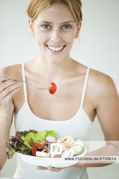Junge Frau isst Salatschüssel