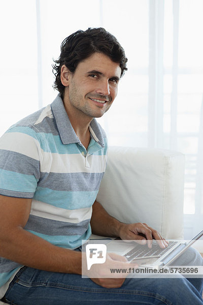 Man holding credit card while using laptop computer  portrait