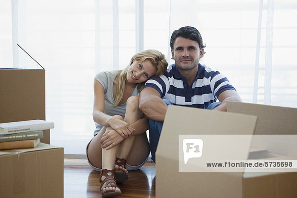 Couple sitting in living room with cardboard boxes