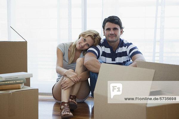 Paar sitzend im Wohnzimmer mit Pappkartons
