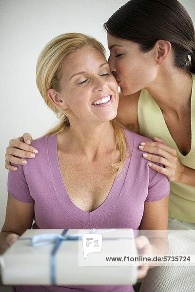 Frau hält Geschenk als Freundin küsst ihre Wange