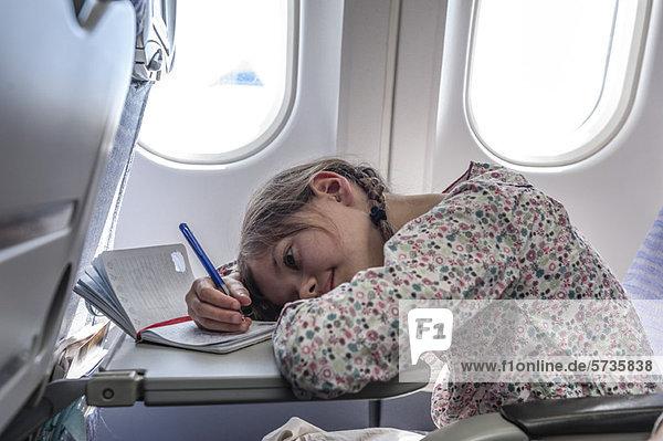 Mädchen ruht Kopf auf Tablett-Tisch im Flugzeug  Schreiben im Tagebuch