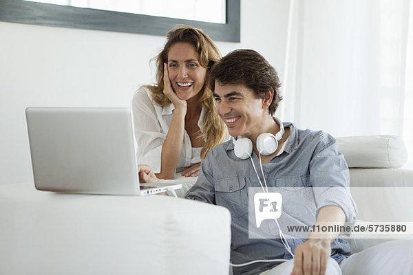 Paar schaut auf Laptop-Computer