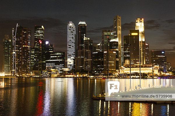 Die Skyline von Singapur bei Nacht von der Promenade aus gesehen