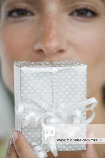 Frau hält Geschenk vor den Mund  abgeschnitten
