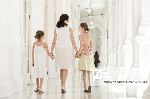 Mutter und Tochter gehen Seite an Seite  Hände haltend  Rückansicht