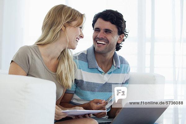 Paare online einkaufen mit Laptop  die sich gegenseitig lachend anschauen