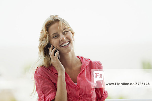 Junge Frau beim Telefonieren  lachend