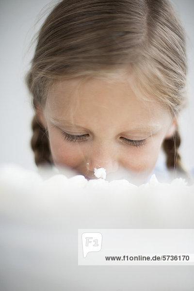 Mädchen mit Kuchenglasur auf der Nase