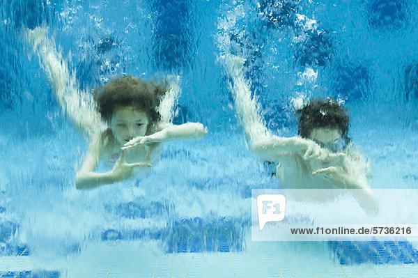 Geschwister schwimmen unter Wasser im Schwimmbad  Hände bilden Fingerrahmen