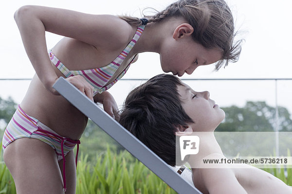 Mädchen im Bikini küssender Bruder auf dem Liegestuhl liegend
