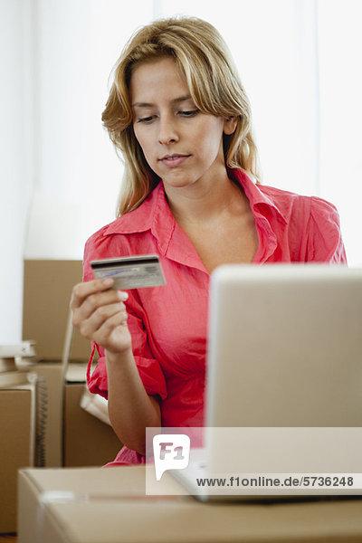 Junge Frau beim Online-Shopping für ihr neues Zuhause