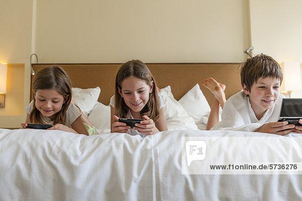 Geschwister spielen Handheld-Videospiele auf dem Bett