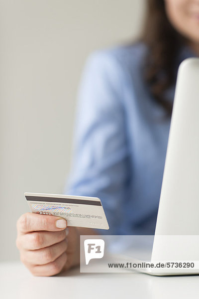 Frau hält Kreditkarte neben Laptop-Computer