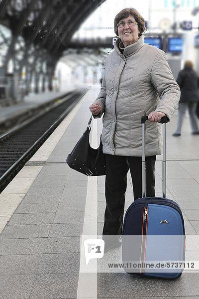 Seniorin mit Koffer wartet auf den Zug im Hauptbahnhof Köln  Nordrhein-Westfalen  Deutschland  Europa