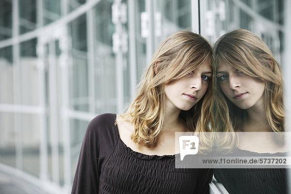 Junge Frau  Porträt  Spiegelung in Glasscheibe