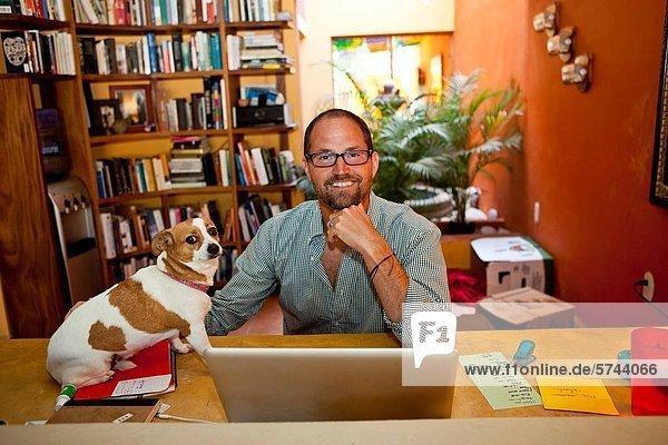 sitzend Mann Schreibtisch Hund Heimarbeitsplatz