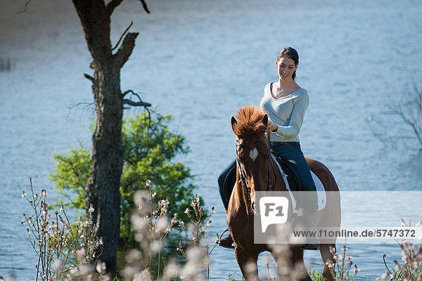 Frau reitet auf einem Pferd am See