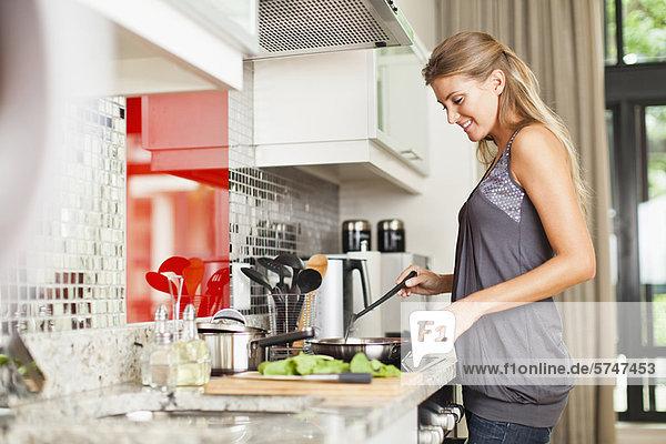 Lächelnde Frau beim Kochen in der Küche 44ddt0059rf