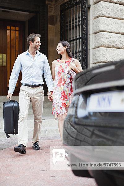 Paar zu Fuß zum Auto auf der Stadtstraße