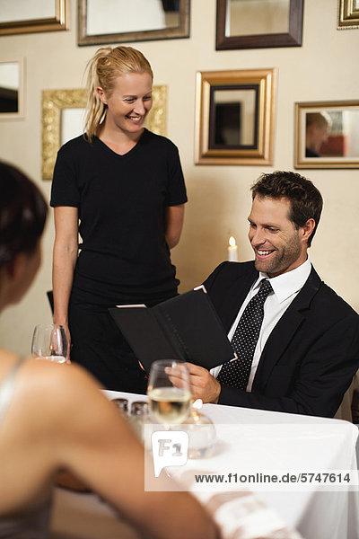 Couple ordering dinner in restaurant