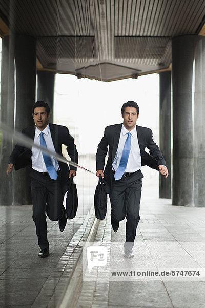 Businessman running on city street