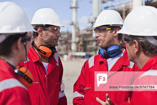 Arbeiter im Gespräch in der Ölraffinerie