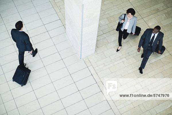 Geschäftsleute beim Gepäckrollen in der Lobby Geschäftsleute beim Gepäckrollen in der Lobby