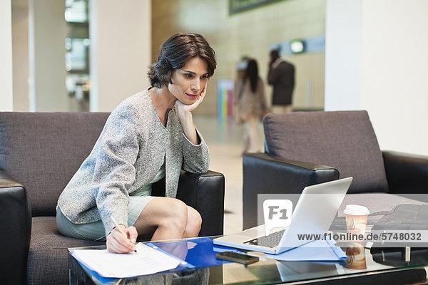 Geschäftsfrau  die in der Lobby arbeitet
