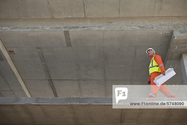 Worker carrying blueprints on site