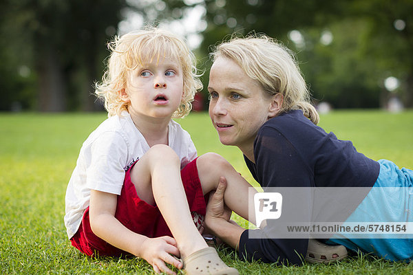 Mother and son sitting in grass