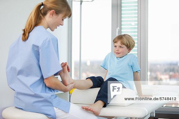 Arzt untersucht die Füße der Jungen im Büro