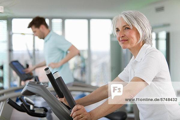 Ältere Frau mit Laufband im Fitnessstudio