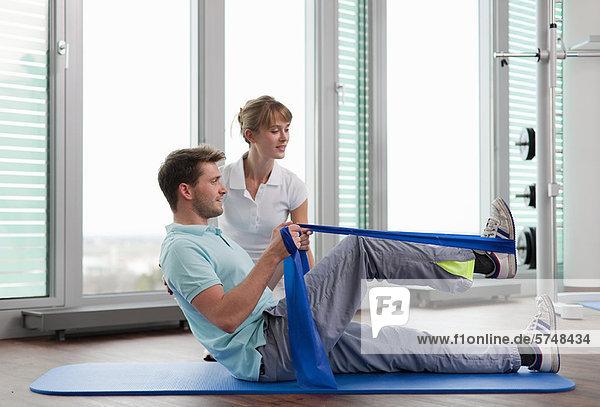 Trainer bei der Arbeit mit dem Mann im Fitnessstudio