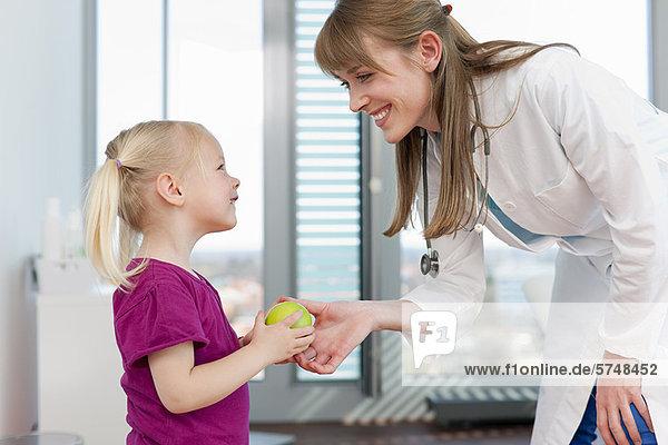 Doctor handing girl an apple in office