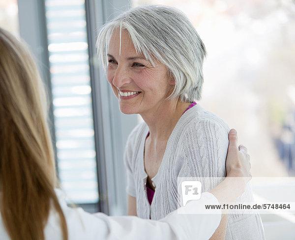 Doktor umarmt lächelnde Frau im Büro