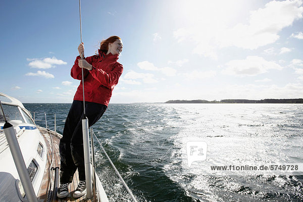 Young Woman holding auf Seil auf yacht