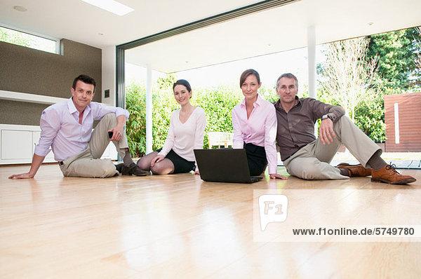 Vier Geschäftsleute sitzen auf dem Boden  Porträt