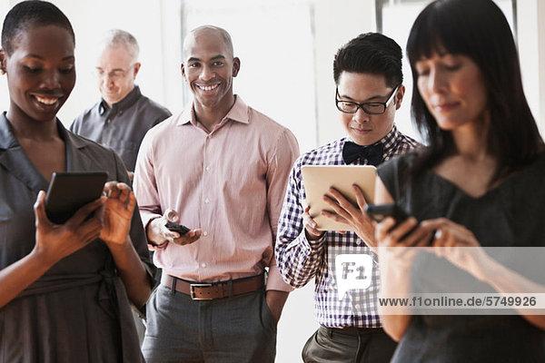 Geschäftsleute mit Handheld-Computern und digitalen Tabletts
