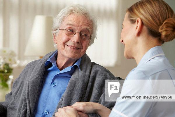 Betreuerin berührt die Hand eines älteren Mannes