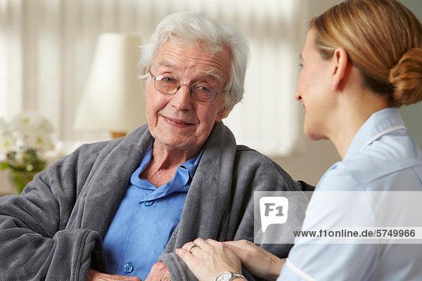 Betreuerin berührt den Arm eines älteren Mannes
