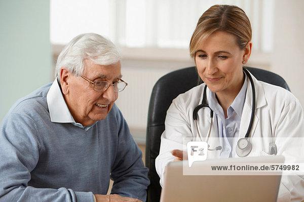 Arzt und älterer Mann beim Betrachten des Laptops