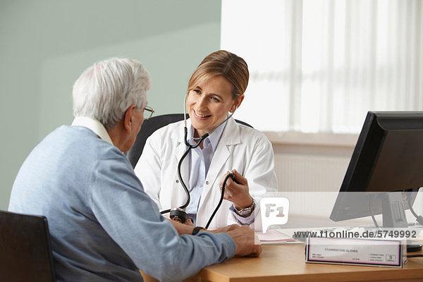 Arzt  der den Blutdruck eines älteren Mannes nimmt