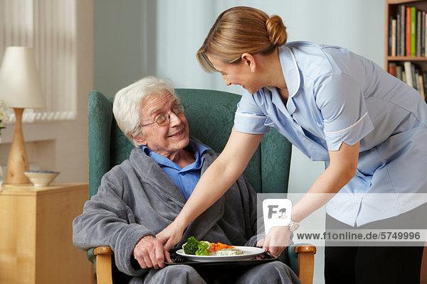 Betreuerin bringt Essen zu einem älteren Mann
