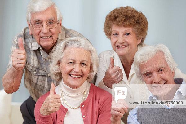 Vier Senioren mit Daumen hoch  Portrait