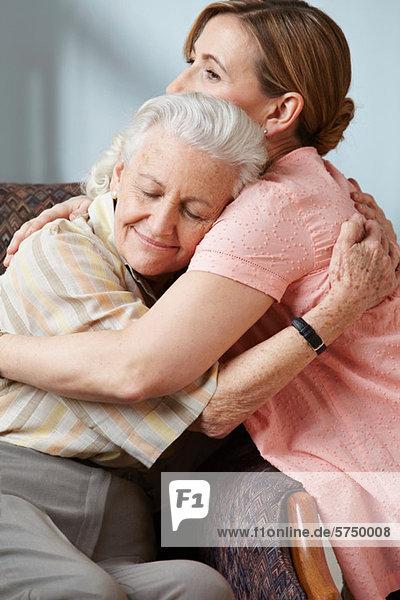 Tochter und ältere Mutter umarmend