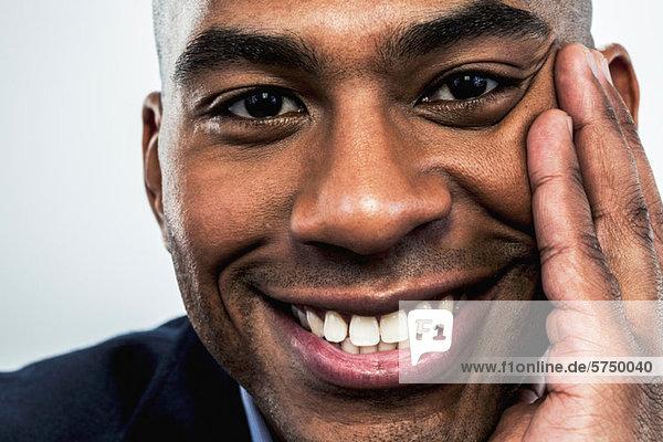 Junger Mann lächelt mit der Hand auf der Wange