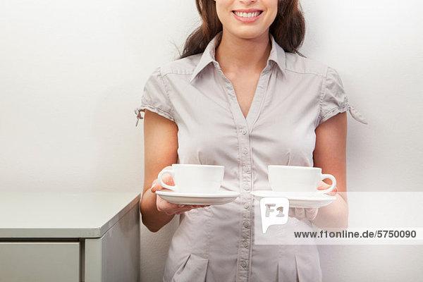 Young Woman Holding zwei Teetassen